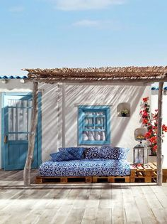 sur la terrasse méditerranéenne facon patio abritée par un toit de paille un canapé diy en palette a été fabriquer pour profiter de l'été du soleil et de la vue sur la mer salon de jardin deco avec palette idee