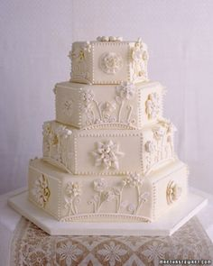 """See the """"Applique Wedding Cake"""" in our Traditional Wedding Cakes gallery Techniques used by dressmakers to turn fabric into flowers inspired this sophisticated cake. A combination of fondant and white chocolate both envelops the cake and decorates it. Prim buttercream dots frame the designs."""