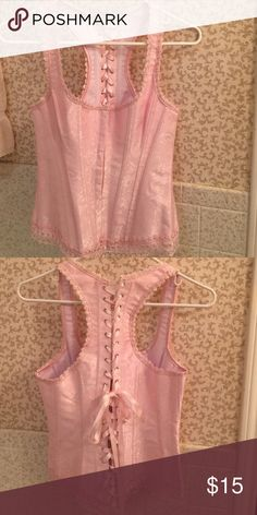Pink corset size small Beautiful baby pink corset never wore this could never fit into this! My loss ! A little make up on one of the pink ribbon but looks like you can wash it out but other than that it's flawless ! half past 12 Tops