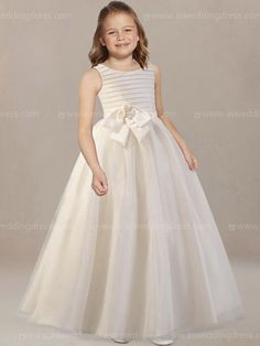 Elegant flower girl dress features round neck and layered pleated bodice, flower accent, full skirt. Hidden back zipper with covered buttons. Available in 60 colors, shown in Ivory.