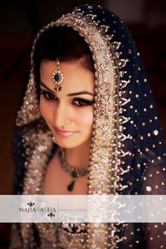 A North Indian bride.  Dupatta or pallu, shaalu covers her head  Maangtikka - A little jewel hanging from the parting on the head upto the forehead