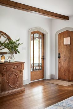 Rich warm wood doors, floors, and antique console glow in a renovated 1927 Tudor style home on Episode 4: Season 5 | HGTV's Fixer Upper: Chip