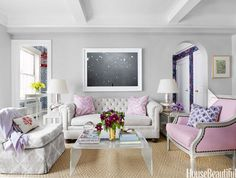Girly living room, pink chair, tufted sofa, lucite coffee table, abstract art, gray walls