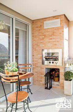 Com parede de tijolinhos e móveis de madeira e ferro, o terraço gourmet tem visual rústico. (Apto 58m²)