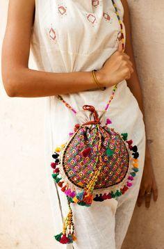 Hermosa bolsa Potli: Es una creación de las mujeres que trabajan en Kalaraksha, una ONG de Kachchh. La bolsa es bordada completa a mano con trabajo de espejo Rabari y cordones.