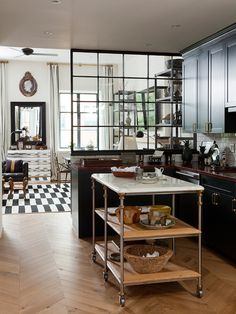 Urban, masculine kitchen by Nate Berkus - black cabinets with brass hardware, wood counters, marble-top rolling island/cart, herringbone floors, steel window divider