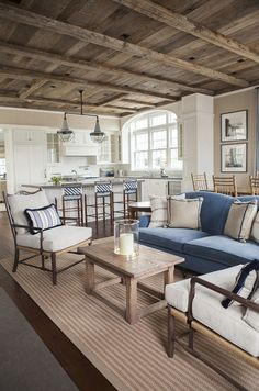 East Coast House with Blue and White Coastal Interiors: The kitchen and dining room opens to a cozy family room with causal furnishings.