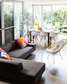 epitome of bringing the outside in -- large windows with plants outside, floral pillows, yellow accents that are in same family as the green leaves outside & orange in pillows