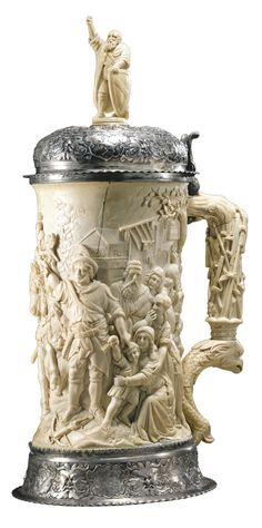 A German silver-mounted ivory tankard the oval barrel finely carved with the legend of William Tell, the ivory handle carved as a trophy of weapons emerging from a coronet above an eagle-headed fish, the finial carved as one of the three founding fathers (Eidgenossen) of the Swiss Confederation, the silver base rim and lid chased wth masks and shields below clusters of fruits   Sotheby's