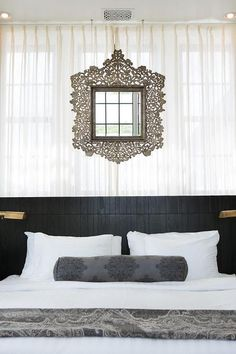 White and black Moroccan style bedroom features walls draped in white sheer drapery panels lined with an ornate mirror placed above a black wood headboard lined with a queen bed dressed in crisp white bedding paired with a black damask bolster pillow as well as a black Moroccan blanket illuminated by aged brass swing arm wall sconces, Studio Swing Arm Wall Lights.