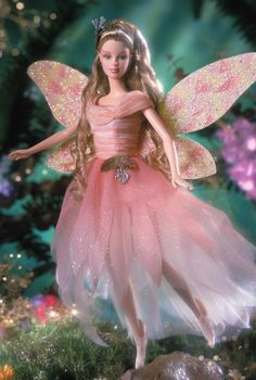 FAIRY OF THE GARDEN Barbie (2001) --- From an enchanted world of fairies, comes our second exquisite and magical fairy friend. Her flowing fairy dress in delicate hues of peach and pink resembles the colors of fragrant flower petals. And the only things sweeter than her pointed fairy ears and pointed fairy shoes, are her amazing wings glistening with special fairy dust. Watching over buttercups and morning glories, she is a garden sprite young and old alike will adore.
