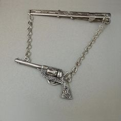 A Wonderful Vintage Mens Tie Bar Clasp Clip in a Western Cowboy Motif featuring a Miniature Sterling Silver Mechanical Gun with Movable Cylinder and