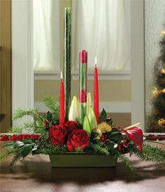 Christmas floral arrangement delivered with red roses, carnations and berries, accompanied by deep green pine, moss and holly. Includes a red pillar candle within an exquisite glass hurricane Christmas Flowers, Christmas Candles, Christmas Things, Christmas Floral Arrangements, Rose Centerpieces, Rose Candle, Christmas Table Decorations, Country Christmas, Pillar Candles
