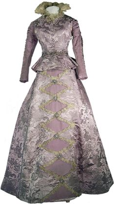 """Silk brocade dress trimmed with glass beads, 1880. Staffordshire Past-Track: """"The lavish brocade design includes stylized honeysuckle flowers. Honeysuckle often symbolised fidelity, affection, and love. It could also represent enjoyment and excess, possibly because of its heady scent. The high neck, tight-fitting bodice, and high shoulders were very fashionable during the 1880s. The skirt would have been supported by a bustle and petticoats. This dress belonged to the Landor family of…"""