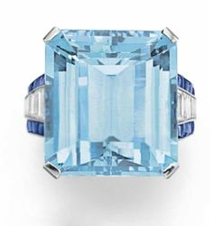 AN AQUAMARINE, DIAMOND AND SAPPHIRE RING   Set with a rectangular-cut aquamarine, to the trapeze-cut diamond and cabochon sapphire shoulders, mounted in platinum