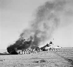 A British Crusader tank passes a burning German Pzkw Mk IV tank during Operation Crusader. 27 November 1941