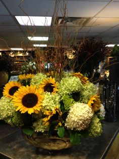 Large centerpiece of limelight hydrangeas, immature green hydrangeas, sunflowers and fresh curly willow.