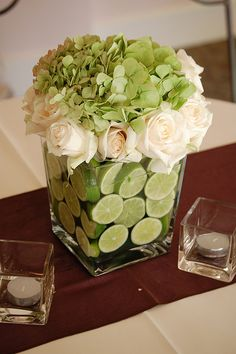 Lime slices, cream roses and green hydrangea centerpiece.