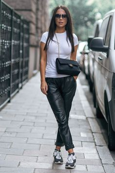 Wear the black and white trend likeJohanna Olsson, and pair a simple white tee with leather trousers and monochrome sneakers. This casual style is perfect for any outing!Trousers: Designers Remix,Tee: ATM,Sneakers/Bag: Chanel.