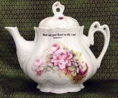 Fine Porcelain teapot with lovely pink rose spray on a white background. This teapot has a very elegant victorian shape with unique handles and a scalloped pedestal base.  Inscribed on the teapot is,
