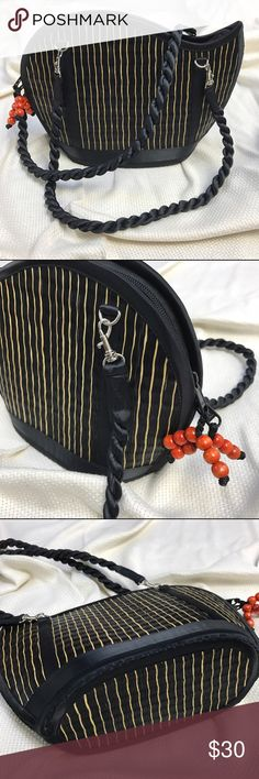 Wave Saraye Tatami Style Woven Purse This unusually shaped bag is from from Baskets of Cambodia and made of woven grass. The main color is black with gold reed stripes. The shoulder strap is of a black satin material that is twirled.Inside the zippered main compartment is a small snap closure pocet, two open pockets, a central zippered pocket and a side zippered pocket. It is 12 in wide, 8.75 in high and 4.5 in deep. (561) Baskets of Cambodia Bags Shoulder Bags
