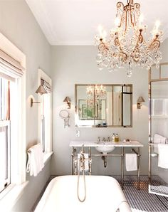 Something about an elegant chandelier over the bathtub.