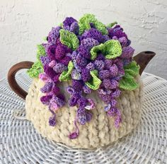 NEW Handmade Tea Cozy Wisteria Flowers Beige Base From Ukrainian DesignerHandmade Tea Cozy from Ukrainian Designer Gorgeous. However I now make a tea cozy for every shape and size. For the base I use a special bulky Chenille Velvet yarn, which I orde Tea Cosy Knitting Pattern, Tea Cosy Pattern, Crochet Home, Crochet Gifts, Knitted Tea Cosies, Tea Cozy, Crochet Flowers, Crochet Projects, Crochet Patterns
