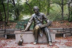 "The bronze statue of Hans Christian Andersen in Central Park. Hans Christian Andersen is reading the story ""The Ugly Duckling"" to the duck sitting at his feet."