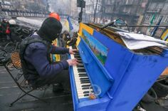 Protester plays piano over the sounds of chaos with riot police in the backdrop.