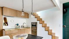 """Il y a mille et une façons d'aménager une cuisine : l'ouvrir sur la salle à manger, y ajouter - ou non - un îlot, l'implanter en """"L"""", en """"U"""", en parallèle ou comme un linéaire le long du mur. Mais savez-vous que la cuisine peut aussi se glisser dans le plus petit recoin, s'inviter sous la mezzanine ou l'escalier, et même se cacher dans un meuble ? La preuve en 15 cuisines de pro résolument déco."""