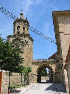Puente St Crucifijo - Puente la Reina-Gares Comme au Moyen Âge, l'entrée dans la ville se fait entre deux tours, vestiges d'une des portes qui s'ouvraient dans les murailles, dont il ne reste pratiquement rien. Puis on passe sous la voûte reliant l'ancien hôpital, qui accueillait les pèlerins, à la « Iglesia del Crucifijo » (l'église du Crucifix), fondée par les Templiers. Le chemin de Saint-Jacques se confond avec la rue principale, la rúa Mayor ou calle de los Romeus.