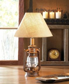 Bring back some old-world style to your living space with this fantastic iron lamp. It features an iron and glass vintage camping-style lantern base and has a burlap neutral shade that will work in any decor.