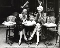 Old black and white shot of two friends drinking coffee and gossiping (for sure) in a Parisian Street Cafe