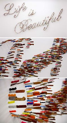 """""""Life is beautiful"""" is written with an accumulation of knives stuck in the wall of the gallery."""