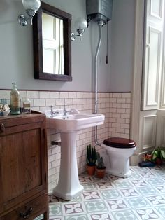 Retro flooring, metro tiles and a high level cistern give this bathroom a beautiful traditional look.
