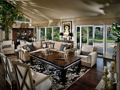 Lovely Asian accents, such as the Chinese coffee table, bring a cultured look to this spacious black and beige great room. Large plants make great use of the high ceilings and get plenty of light by the wall of glass doors. A plush sectional creates a cozy seating area within the larger space.