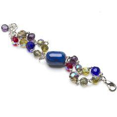 Ajustable, confeccionada con piedra semipreciosa central Jade y cristales en tonos azul, colorado, gris humo, amatista y oliva.