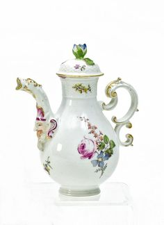 Small Jug with Mascaron.   Meissen. Circa 1750/60.     Porcelain, enriched in colours and in gilt. Pear-shaped with double-C handle. The nozzle has an applied mascaron decor and the spout is shaped like a dragon's head. Height 16cm.  Crossed swords mark.