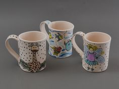 Marcia Eagers mugs adorned with her hand drawn whimsical images. She is our Featured Artist for July. See more of her work in our Gallery.  #ceramics #artisan #pottery #clay #MadeinCT #MadeinAmerica #mugs #gifts