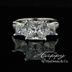 MiaDonna- The Happy Three Stone Engagement Ring holds the Simulated Diamond Hybrids in prong setting a top a smooth edge shank. Your choice of center stone shape, set with 2 x PRINCESS cut sides. All our Man Made Diamond alternative jewelry is created in Eco Friendly precious metals.