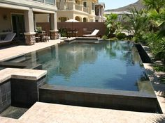 Beautiful contemporary pool.  To complement the dark interior of this perimeter overflow pool, charcoal black tile was used to face the weir wall and the raised bond beam.