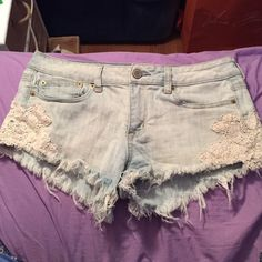 AEO light wash denim shorts Light wash with lace detail on the sides. Perfect condition! Perfect for the summer! Stretch material size 8 American Eagle Outfitters Shorts Jean Shorts