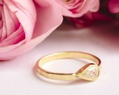 This extraordinary engagement piece recalls the royal jewelry of ancient times, with a .30 carat, pear-shaped diamond horizontally set in a hand-built gold bezel. The substantial 2x1mm hammered gold band catches the light in any space, its weighty golden presence and precious stone making the Monarch Engagement Ring a crowning glory.Details:Pear-shaped diamond, set horizontally, hand-crafted bezel Pear Diamond Engagement Ring, Pear Diamond Rings, 3 Carat Diamond, Pear Shaped Diamond, Diamond Studs, Hammered Gold, Royal Jewelry, Conflict Free Diamonds, Gold Bands