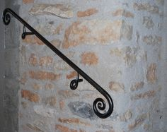 A short, wrought iron handrail with an interesting twist fixing it to the stone wall.