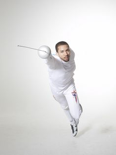 [ID: an epee fencer with his mask off, fleching at the camera.] Ben Bratton! Photo by Mike Dote.