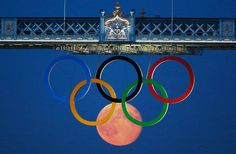 The full moon rises through the Olympic Rings