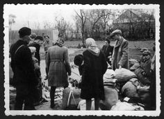 Jews standing by their belongings, next to Slovakian militiamen. They will soon be marched out and murdered