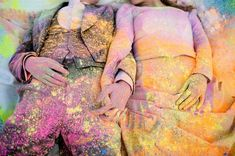 Bride and groom covered in holi powder laying in the snow