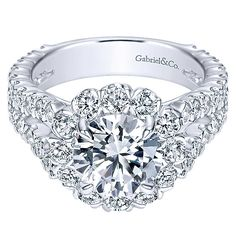 18K White Gold Split Shank Floral Halo Diamond Engagement Ring. This ring features 2.03cttw of round diamonds with a substantial split shank of pave set round diamonds. Features a large round floral h