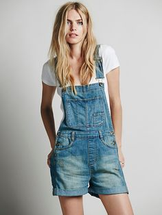 Boyfriend Shortall | Distressed denim short overalls with relaxed boyfriend fit and four pocket design. Bib features additional pockets. Button detailing at hips and adjustable shoulder straps. Cuffed hems.